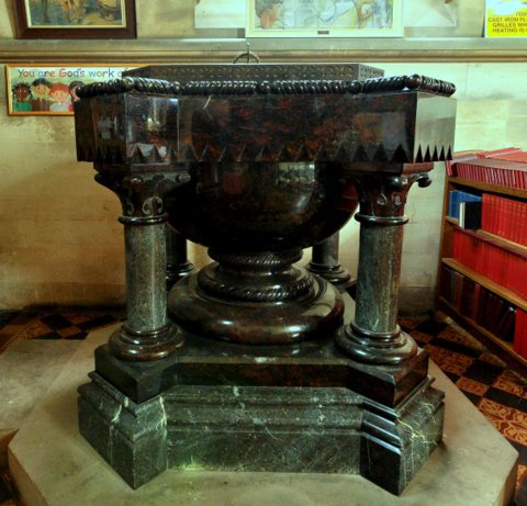 The wonderfully heavy font is Red Cornish serpentine on a granite plinth. Its lid is so heavy it needs two strong men to lift it when the font is needed for a baptism (Brian Belton)