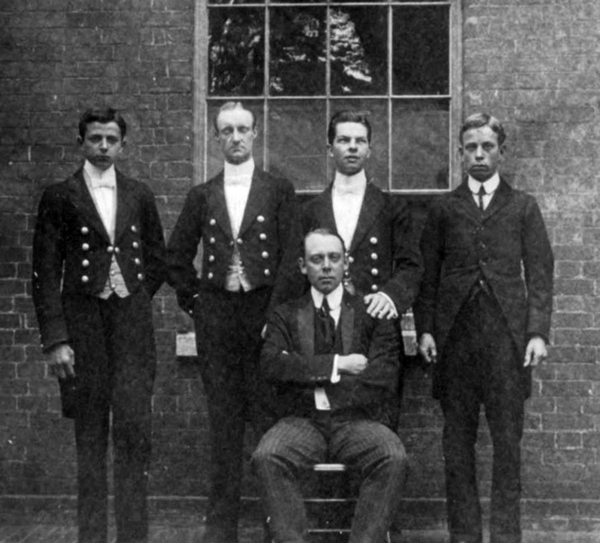 Denbies footmen in their livery of chocolate with red piping. The brass buttons bear the Cubitt crest and a coronet. The seated man may be the underbutler, or the butler, although the familiarity of a footman's hand on his shoulder makes this latter suppostion doubtful (Ranmore Archive)