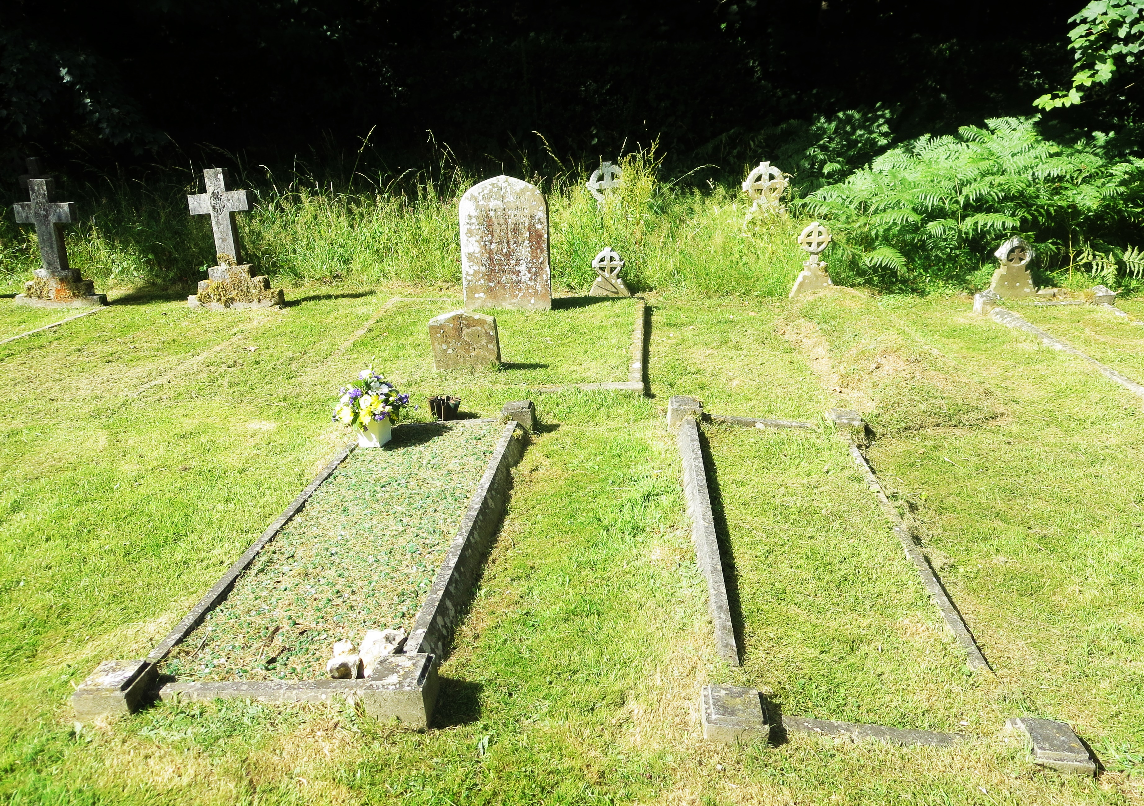The Buckland and Overton graves. James and Margaret Annie Buckland are buried in the grave with the flowers; James (senior) and Annie Adelaide are to the right, and two rows behind with matching ?Celtic cross headstones are Annie Adelaide's parents Thomas and Ann